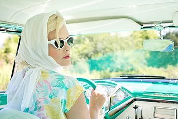 coche vintage conducido por mujer rubia años 50